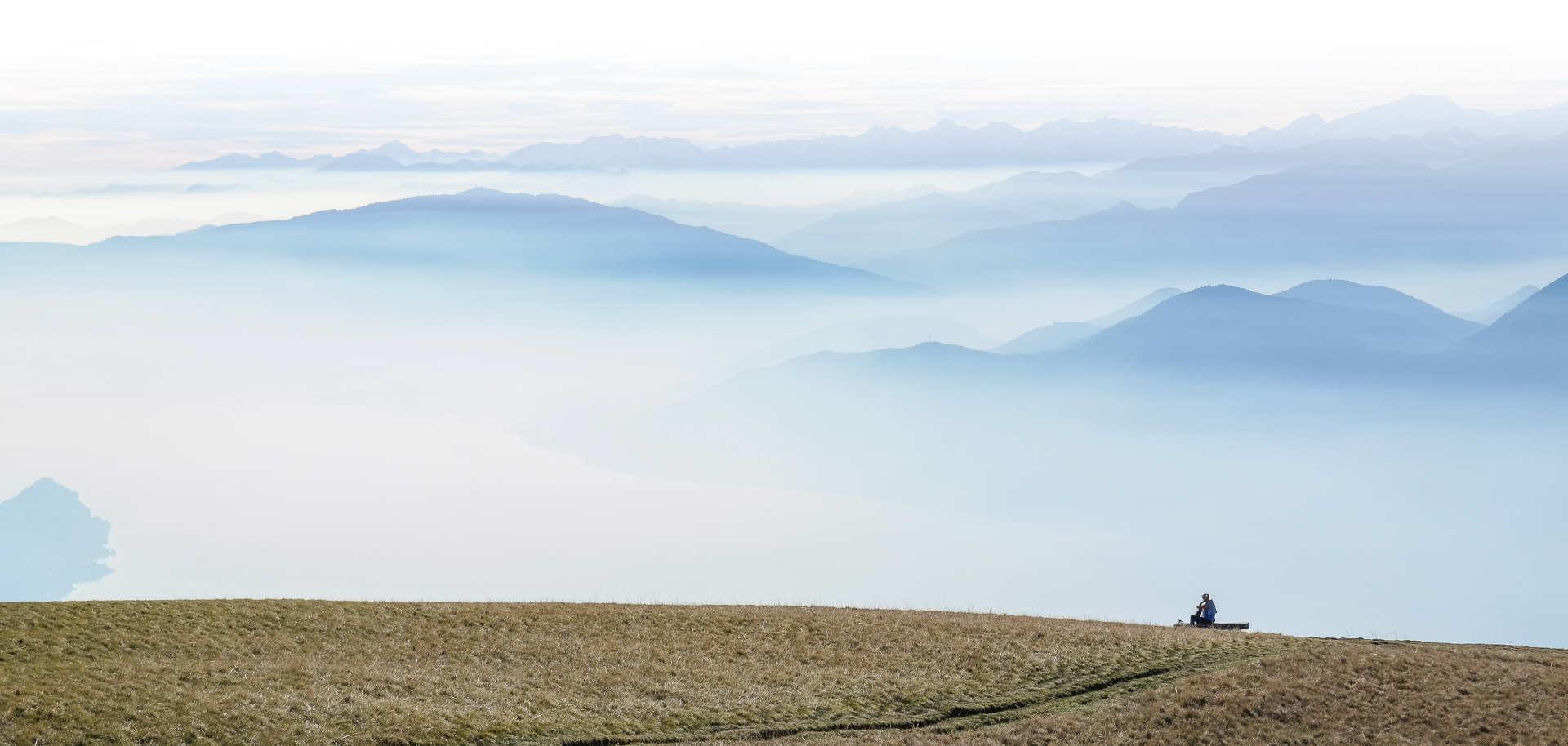 Persona sentada observando paisaje montañoso